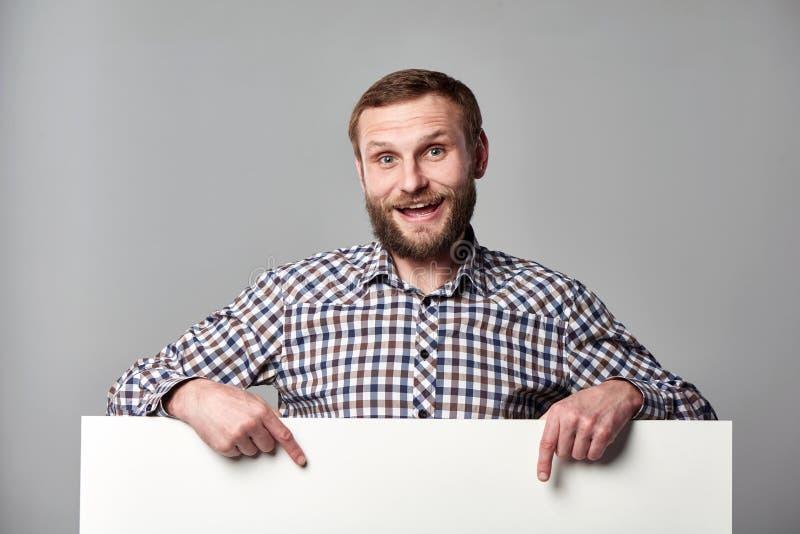 有whiteboard的激动的有胡子的人指向空白的拷贝空间的 库存照片