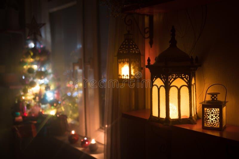 有xmas树的自由空间书桌和灯在家 圣诞节灯笼在窗口附近的选择聚焦与充分假日树  图库摄影