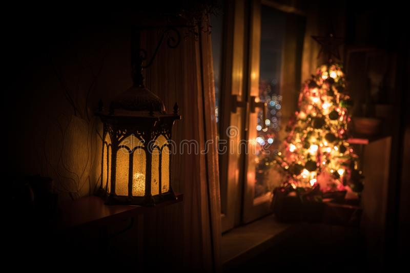 有xmas树的自由空间书桌和灯在家 圣诞节灯笼在窗口附近的选择聚焦与充分假日树  免版税图库摄影