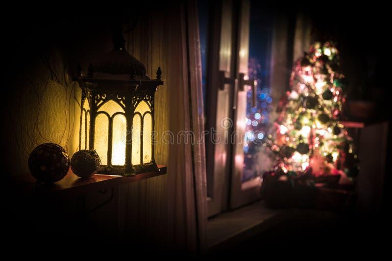 有xmas树的自由空间书桌和灯在家 圣诞节灯笼在窗口附近的选择聚焦与充分假日树  免版税库存图片