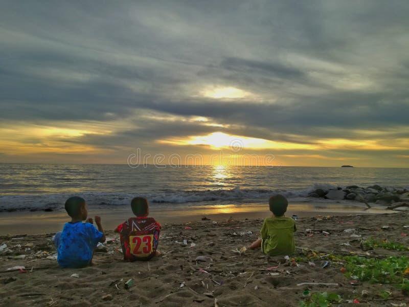朋友、海、日落和垃圾 库存照片
