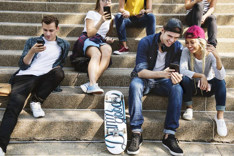 朋友一起坐楼梯使用智能手机和 免版税库存照片
