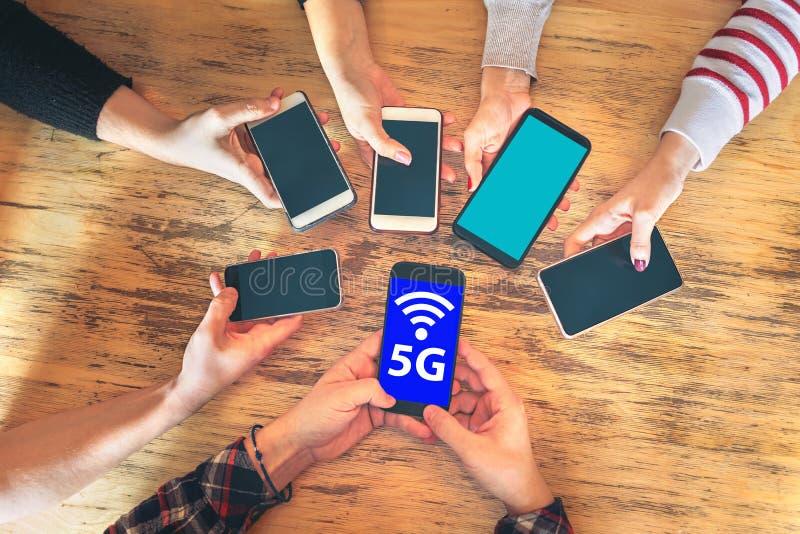 朋友一起编组获得乐趣使用5G在智能手机的网络连接,分享无线连接的手细节 库存照片