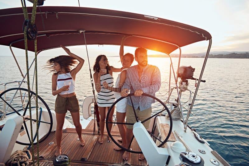 朋友享受在游艇的假期 在一条风船的党在日落 库存图片