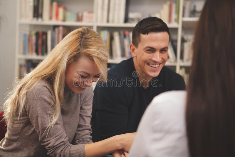 朋友享用一起学习在图书馆的小组 库存图片