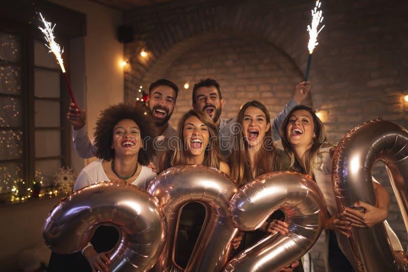 朋友们欢庆新年除夕,与玩火者挥手,拿着2020个气球 免版税库存照片