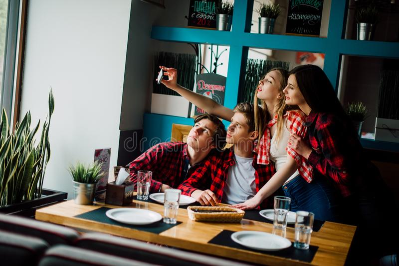 朋友做在咖啡馆的selfie 两个男孩和两个女孩做在咖啡馆的selfie 库存照片