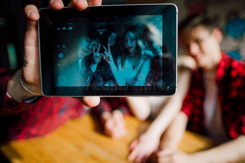 朋友做在咖啡馆的selfie 两个男孩和两个女孩做在咖啡馆的selfie 免版税库存图片
