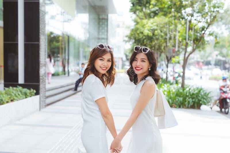 朋友去购物 在商城的两个少妇步行与 库存照片