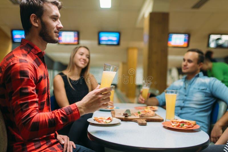 朋友喝并且吃在滚保龄球的俱乐部的比萨 库存图片