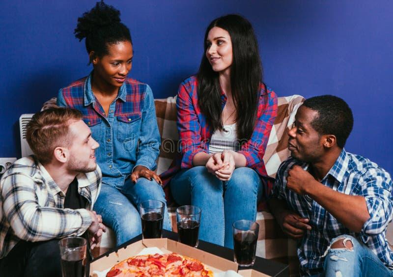年轻朋友在家坐长沙发用新鲜的薄饼 免版税库存图片