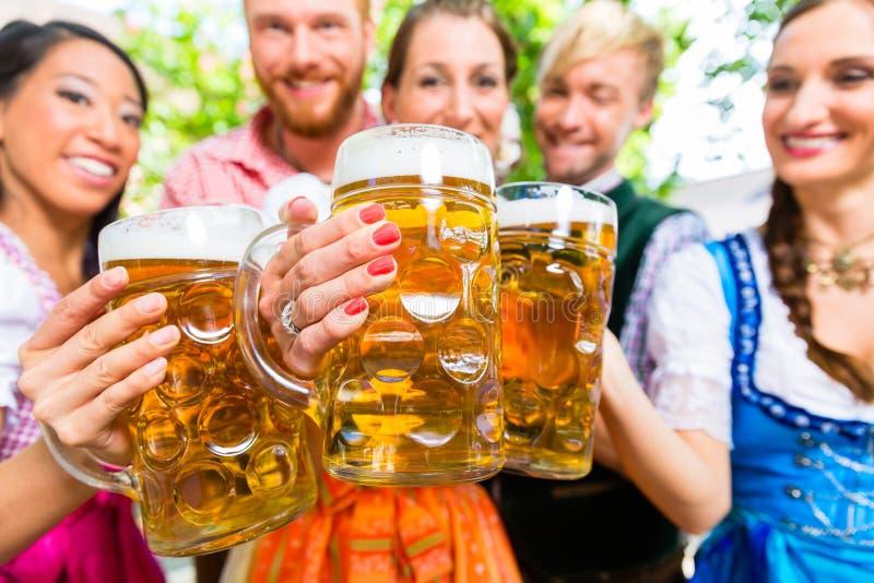 朋友在有啤酒杯的啤酒庭院里 库存照片