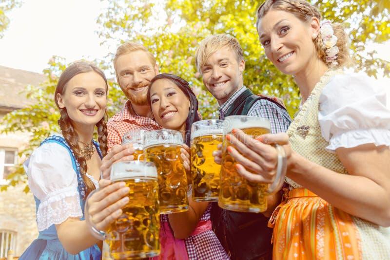 朋友在有啤酒杯的啤酒庭院里 图库摄影