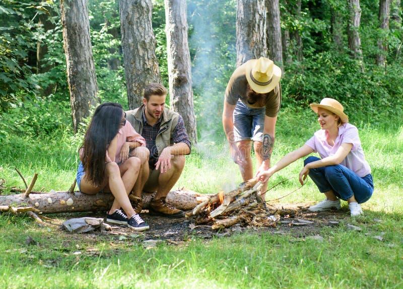 朋友在朋友去野餐的森林公司中享用周末烤肉或在篝火附近烤烧烤食物 最好的朋友 库存照片