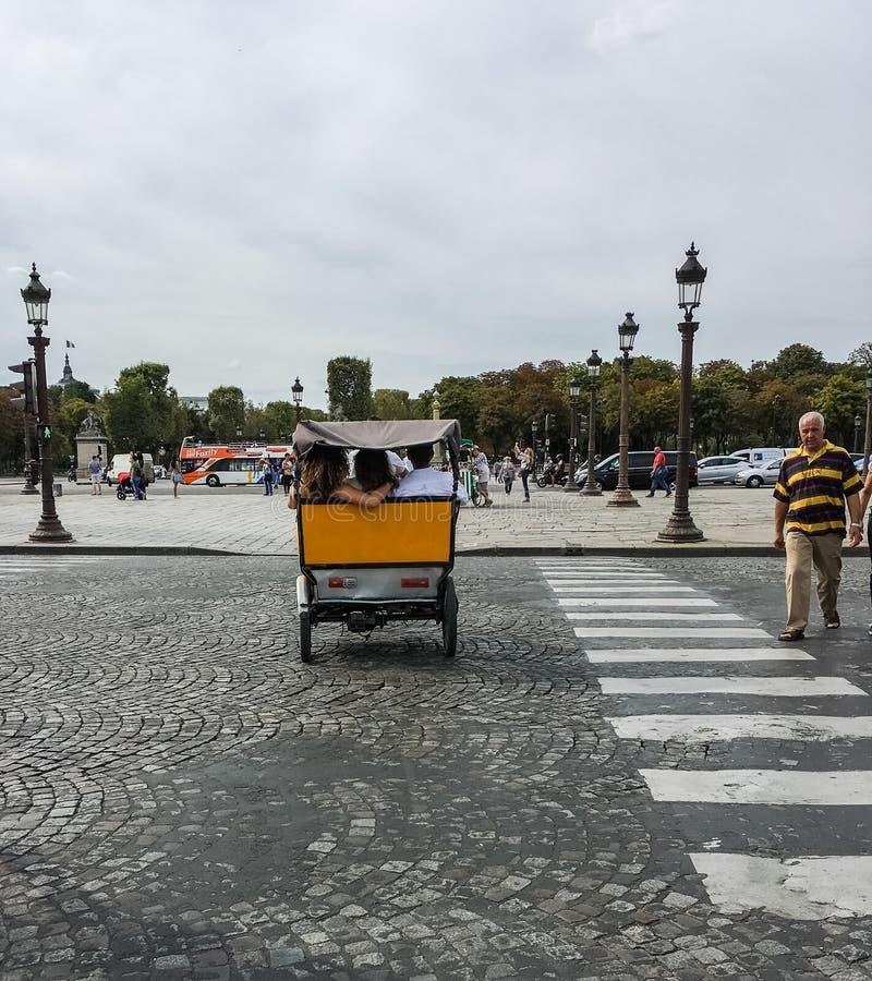 朋友在自行车小室背后乘坐在协和广场,巴黎 库存图片