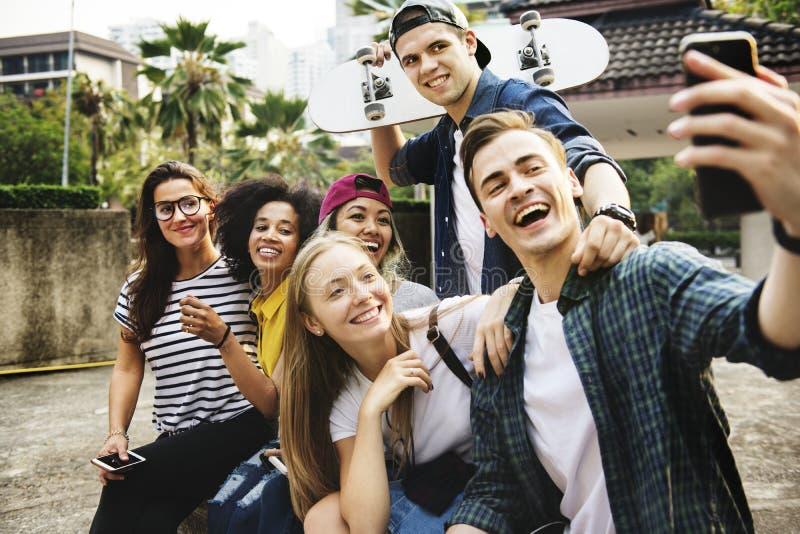 朋友在采取小组selfie千福年和青年时期c的公园 库存照片