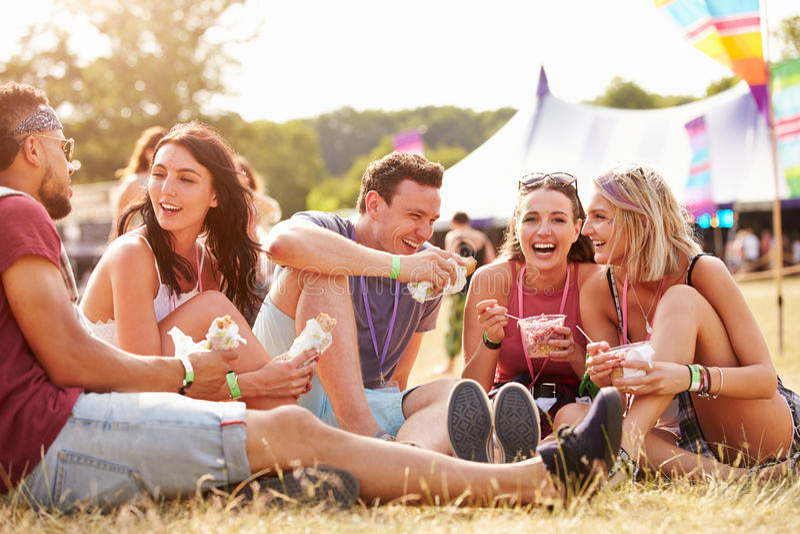 朋友坐吃在音乐节的草 免版税库存照片