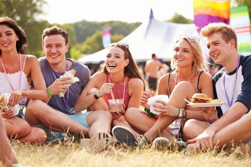 朋友坐吃在音乐节的草 免版税库存图片