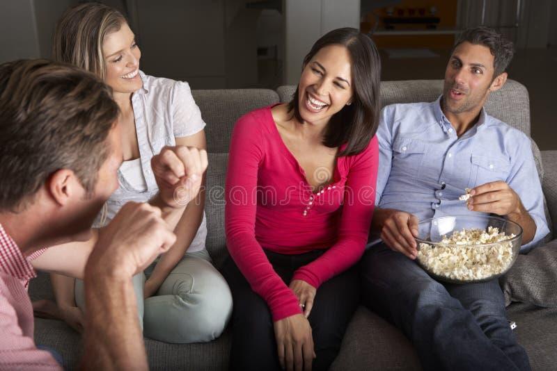 朋友坐沙发谈和吃玉米花的小组 免版税库存照片
