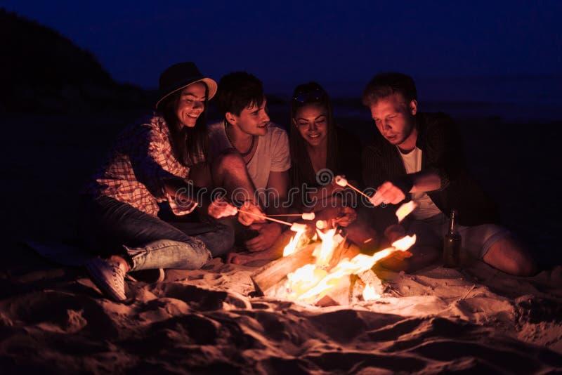 朋友坐海滩在篝火附近使玻璃叮当响 图库摄影