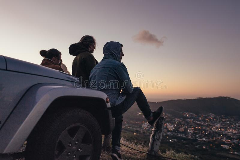 朋友坐看下面城市的小山顶 免版税图库摄影