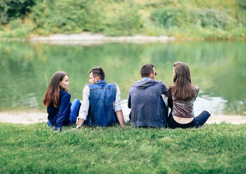 朋友坐草由公园后面视图的湖 免版税库存图片