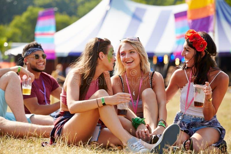 朋友坐草谈话在音乐节 免版税库存图片