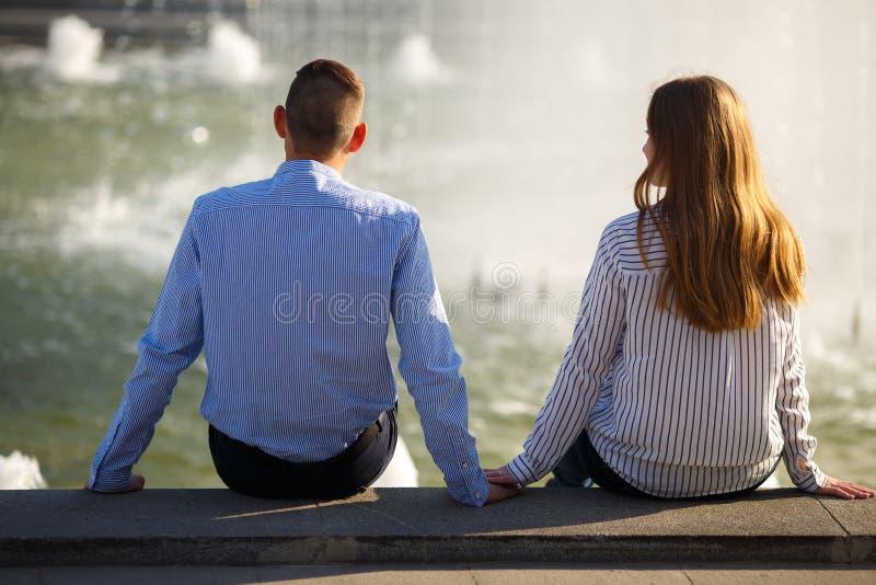 朋友坠入爱河 坐在喷泉hol附近的年轻害羞的人民 库存图片