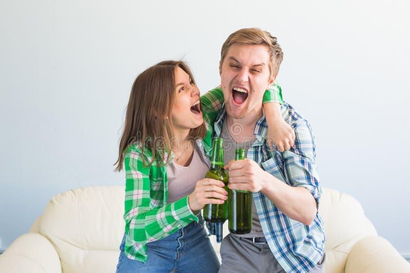 朋友夫妇在沙发观看的体育比赛坐电视 免版税库存图片