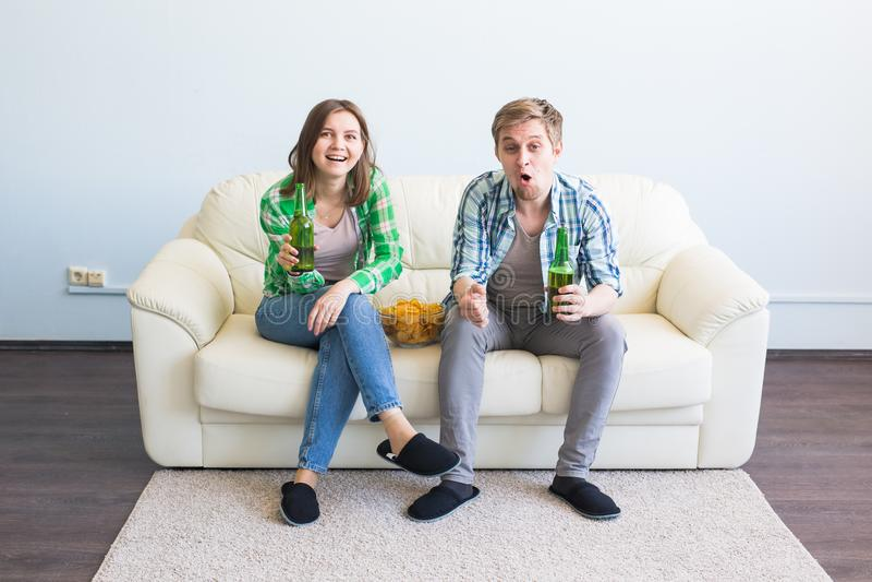 朋友夫妇在沙发观看的体育比赛坐电视 免版税库存照片