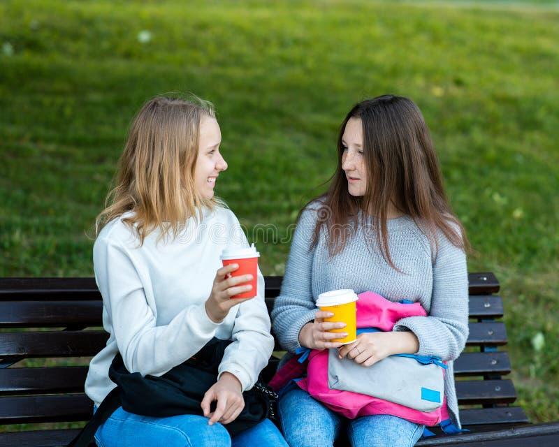 朋友女孩二 在长凳的夏天 他们谈话用拿着咖啡和茶的手 女小学生休息 免版税库存图片