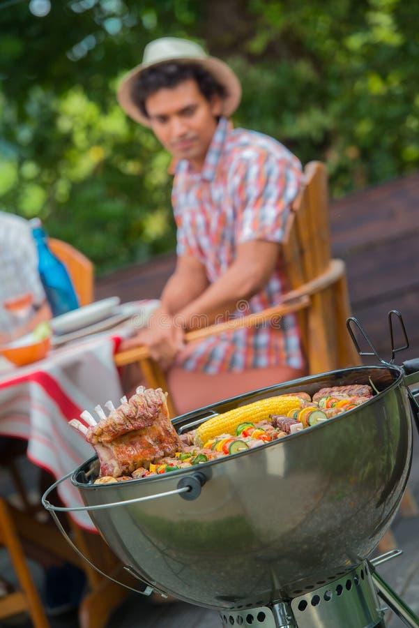 朋友愉快在烤肉期间在家庭庭院BBQ 免版税图库摄影