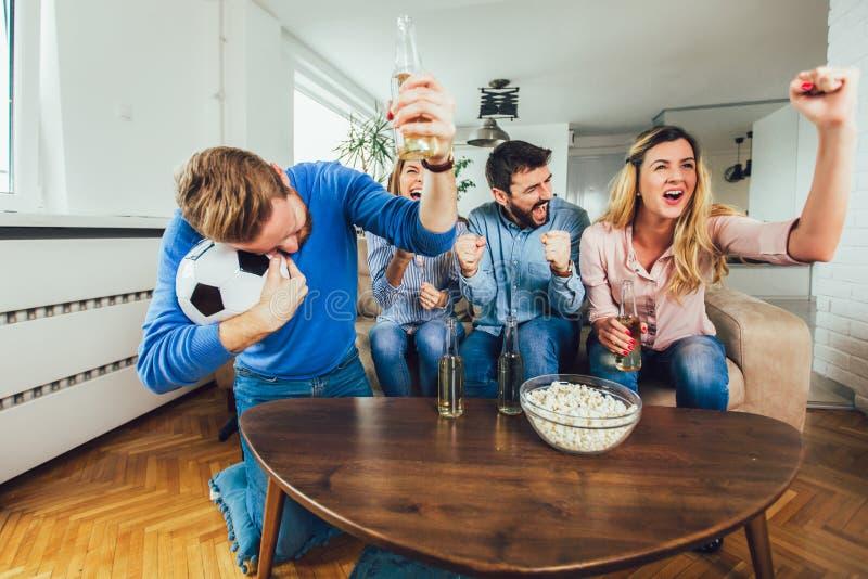朋友或观看在电视的足球和在家庆祝胜利的足球迷 友谊、体育和娱乐概念 免版税库存图片