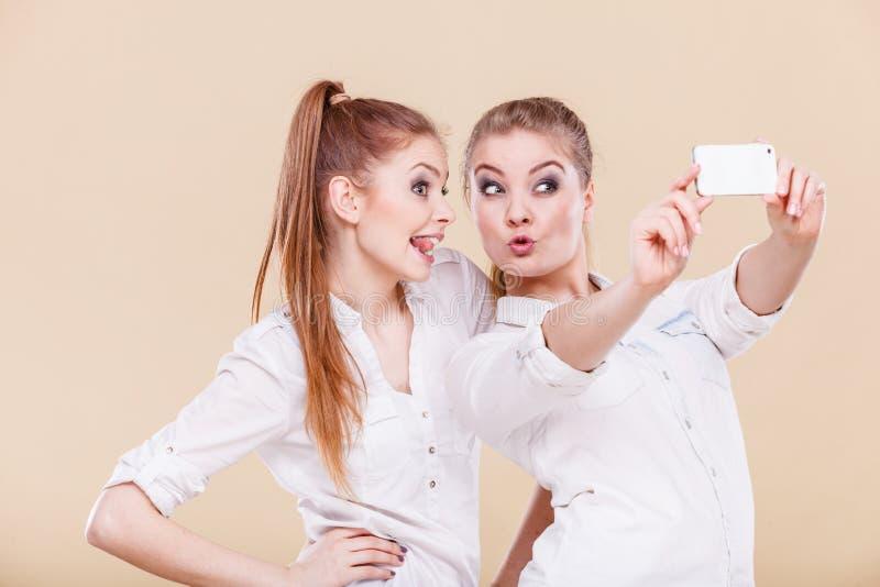 朋友拍与巧妙的电话的学生女孩自已照片 库存图片