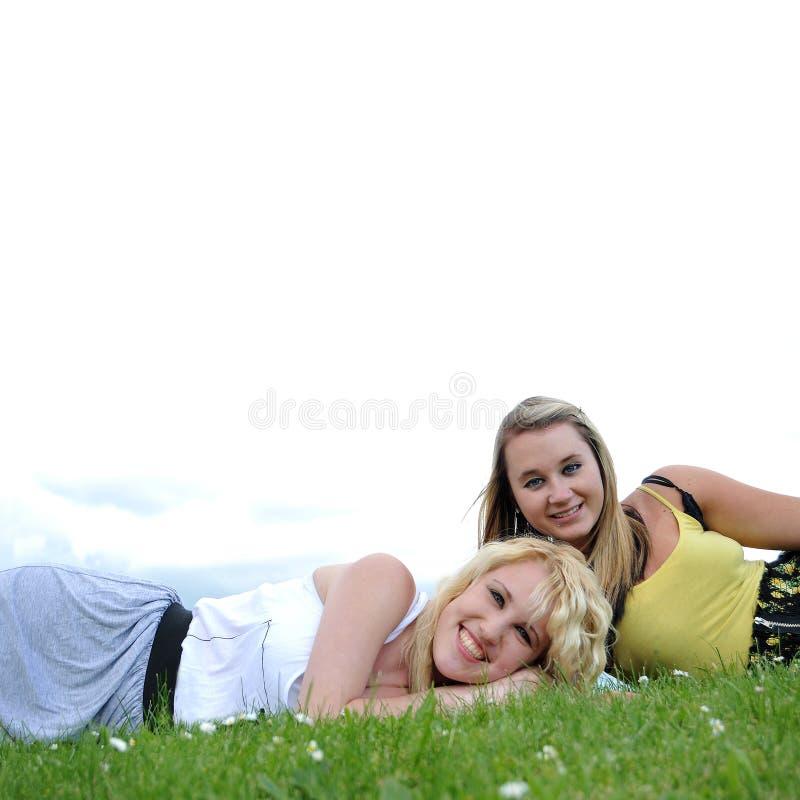 朋友放置二的女孩草 免版税库存照片
