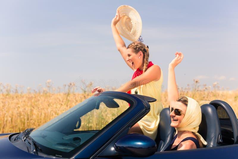 朋友有夏天兜风在敞篷车汽车 免版税库存图片