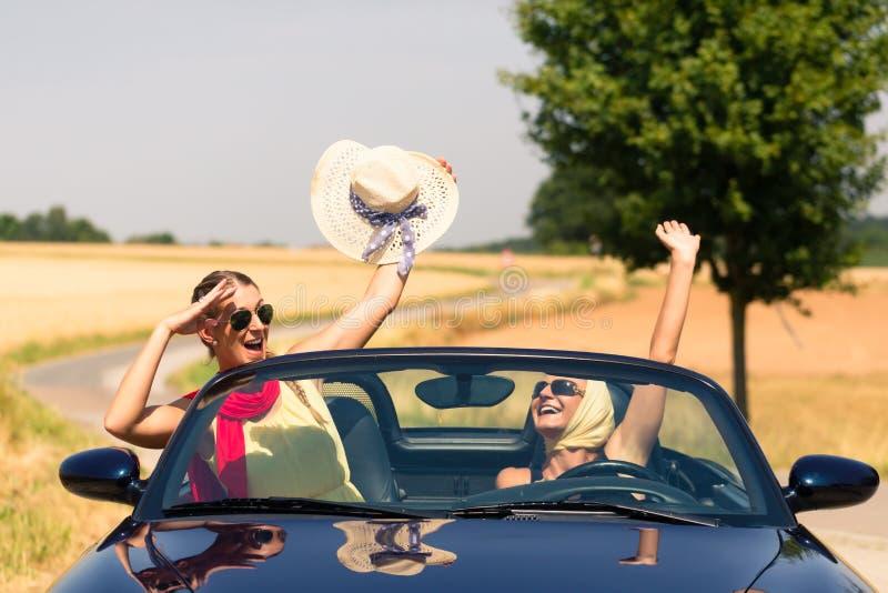 朋友有夏天兜风在敞篷车汽车 免版税库存照片