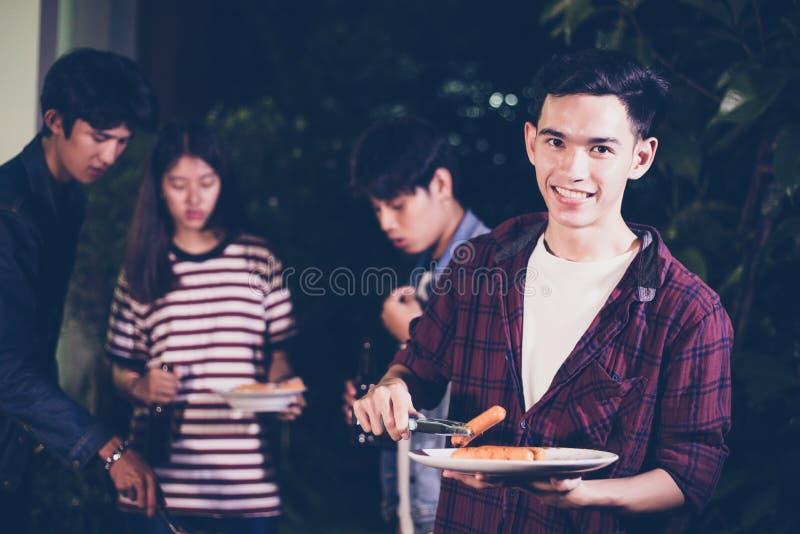 朋友有室外庭院烤肉笑w的亚洲小组 免版税图库摄影