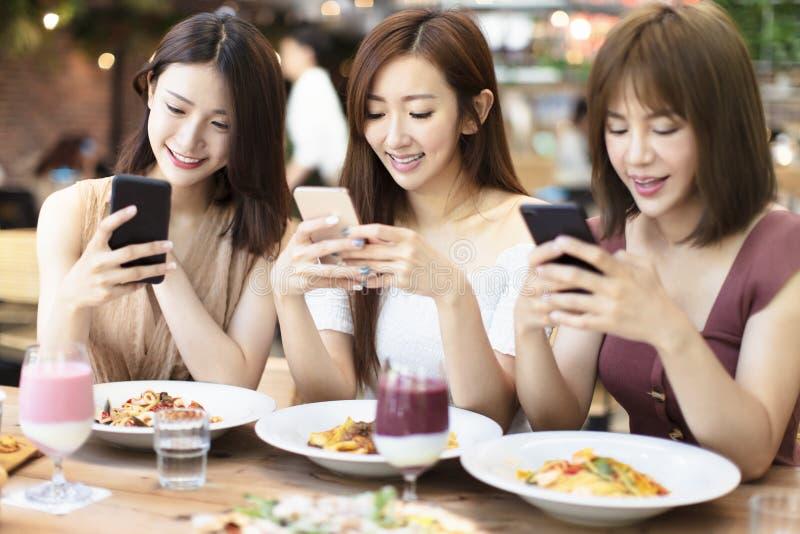 朋友有晚餐和观看智能手机在餐馆 图库摄影