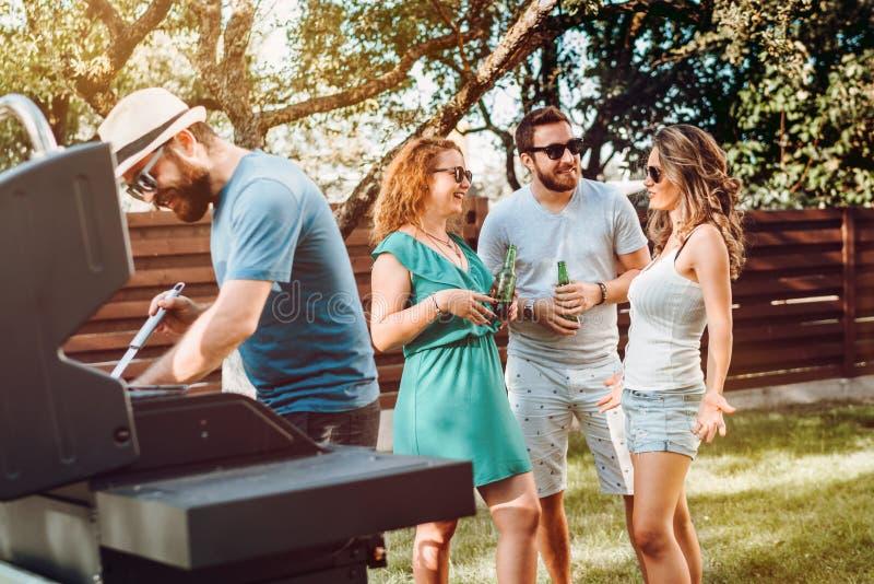 朋友有烤肉在后院 享受一个星期天晚上的小组白种人朋友 免版税库存图片