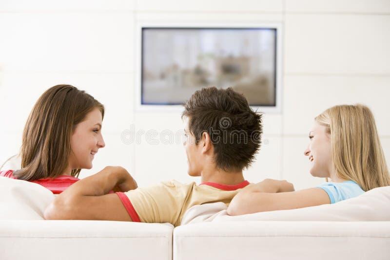 朋友注意客厅的电视三 图库摄影