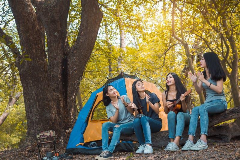 朋友编组年轻亚洲妇女野营 库存图片