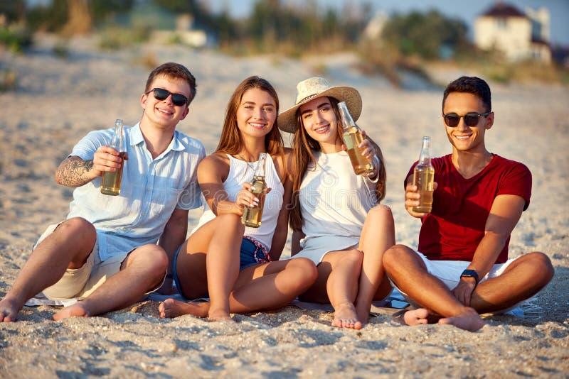 朋友获得乐趣享用饮料和放松在海滩的小组在日落在慢动作 年轻人和妇女 图库摄影