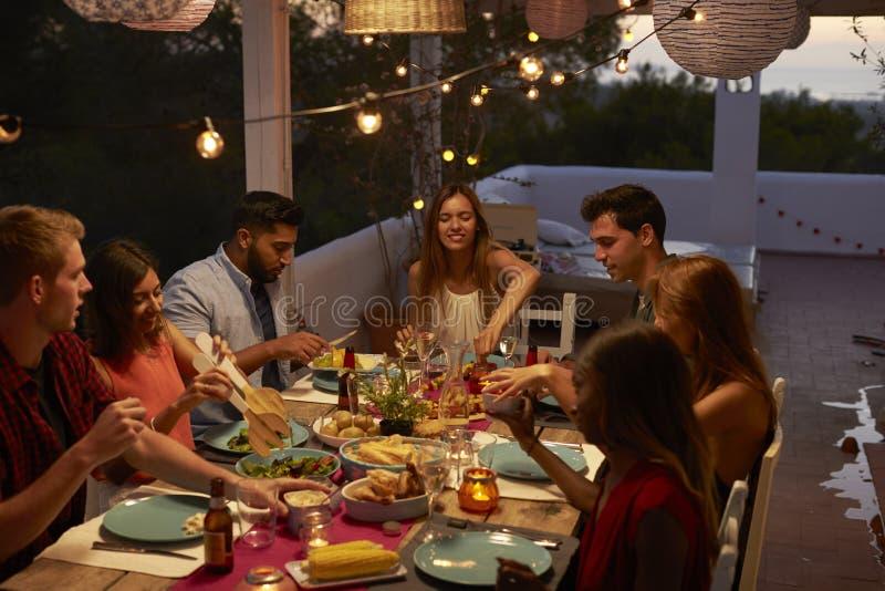 朋友谈话在露台的一次晚餐会,高的看法 库存照片