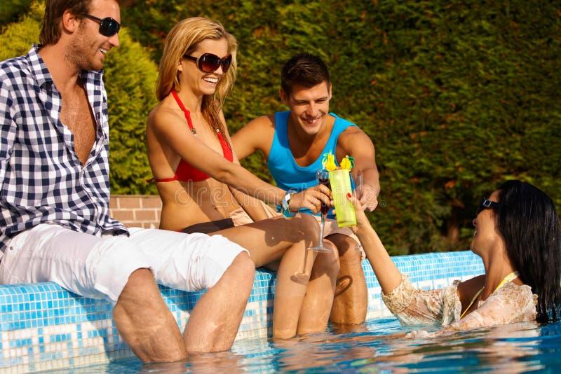 年轻朋友通过游泳池微笑 库存图片