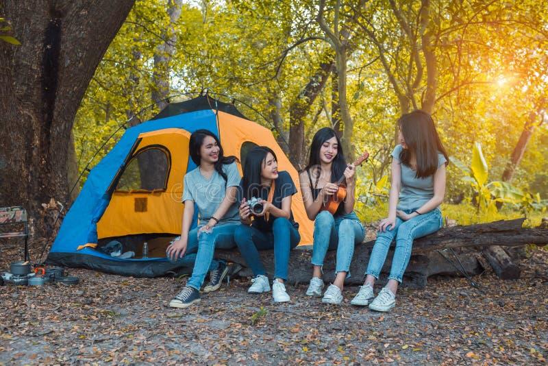 朋友野营和休息在森林的编组年轻亚裔妇女演奏尤克里里琴 库存照片