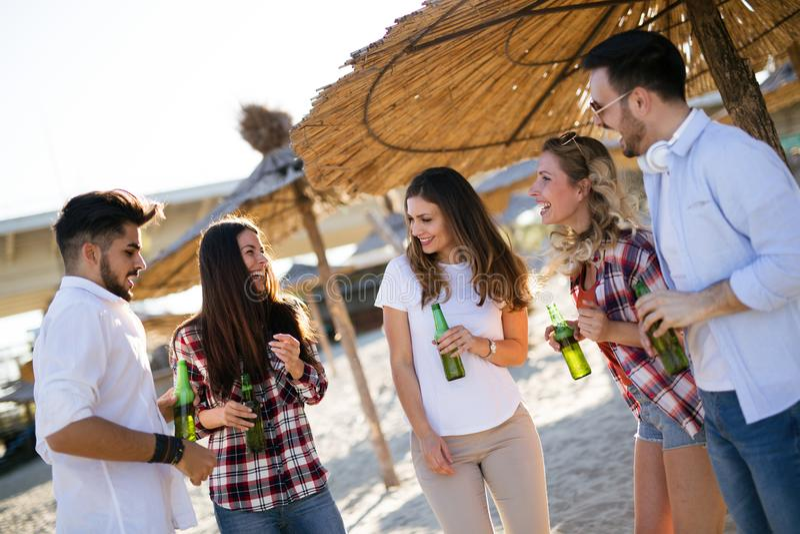 朋友集会和获得在海滩的乐趣在夏天 库存图片