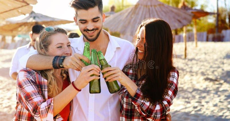 朋友集会和获得在海滩的乐趣在夏天 免版税图库摄影