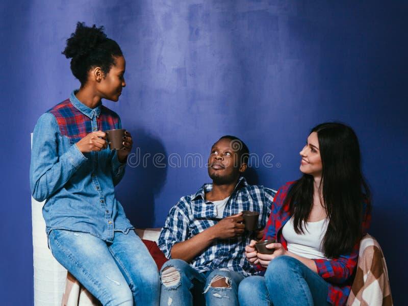 年轻朋友饮料咖啡,人种间友谊 图库摄影