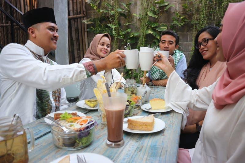 朋友饮用茶多士在桌上用餐在赖买丹月期间的小组 免版税图库摄影
